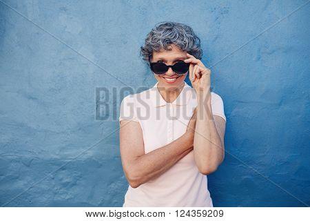 Smiling Mature Woman Peeking Over Sunglasses