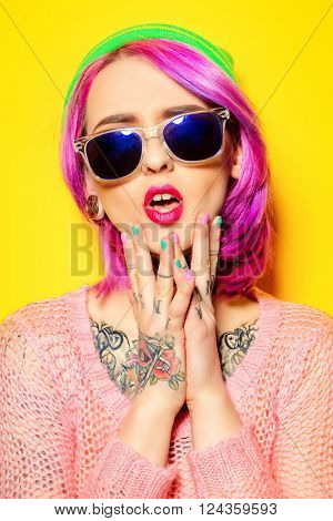 Bright fashion concept. Trendy girl with crimson hair wearing bright clothes and sunglasses alluring by a  yellow background. Optics style. Tattoo.