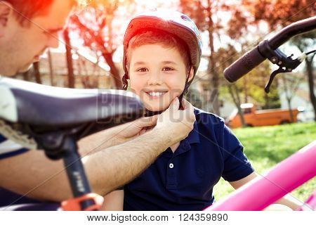 Boy putting on a bike helmet closeup picture
