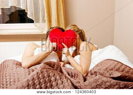 Couple sitting in bed and covering faces with heart pillow