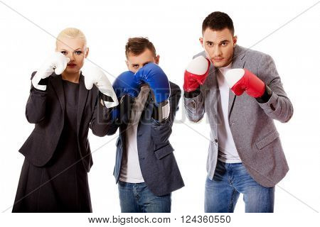 Three business people wearing boxing gloves
