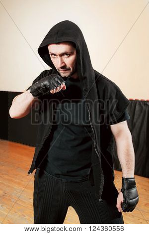 Aggressive mid adult  street fighter in black sport cloth. Street fighter in training gloves staying in gym and looking at camera with threat.  Mid adult man healthy sport lifestyle concept.