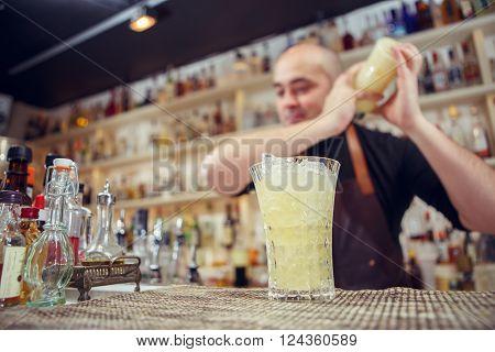 Barman at work. Shaking cocktail in shake.