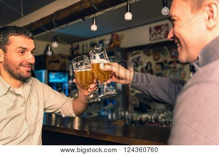 Friends in bar having good time, toasting with beer ** Note: Visible grain at 100%, best at smaller sizes