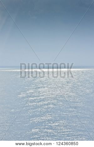 Sea surface with sun rays an blue sky