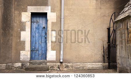 Blue door and drain pipe on exterior wall