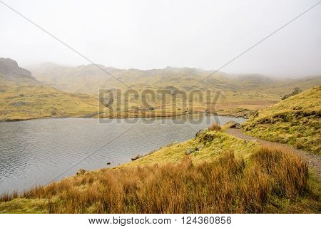 Green grass covered mountains with distant hikers walking on a trail around a small mountain lake.
