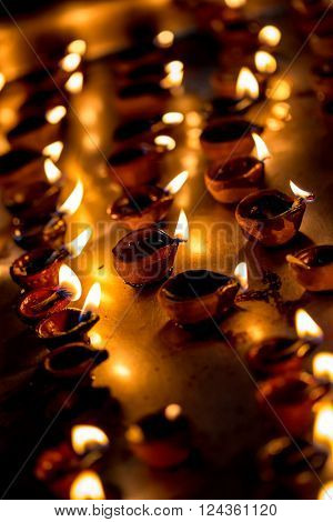 Burning candles in the Indian temple. Diwali the festival of lights. Warning - authentic shooting with high iso in challenging lighting conditions. A little bit grain and blurred motion effects.