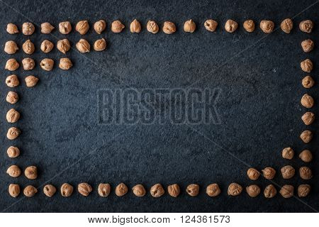 Frame of chick-peas on the dark stone background
