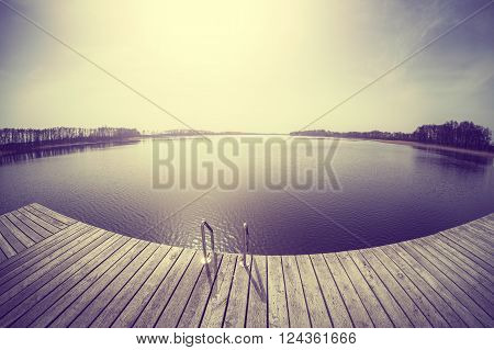 Vintage toned fisheye lens picture of a wooden pier Lake Osiek in spring Poland.