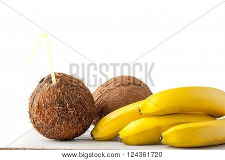 Coconut with straw and bananas on the white table