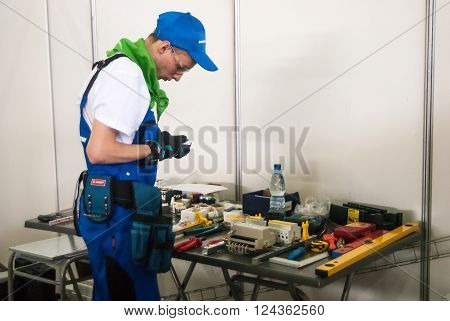 Tyumen, Russia - March 23. 2016: Open championship of professional skill among youth. World skills Russia Tyumen - 2016. Young electrician performs a task of professional competition