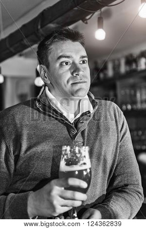 Portrait of a serious mid adult man having beer in pub