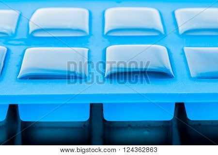 Ice cube tray with ice close-up horizontal