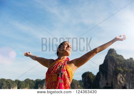 Blissful woman relaxing and enjoying freedom on Thailand travel vacation in Krabi.