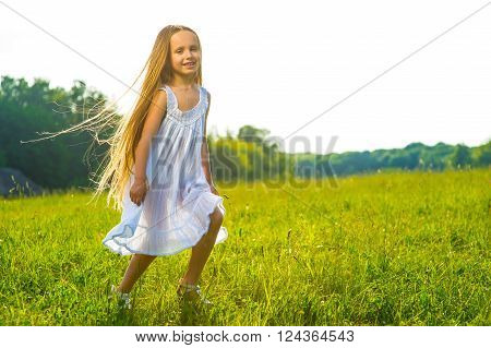 Girl ran across the lawn. Child on the background of nature.
