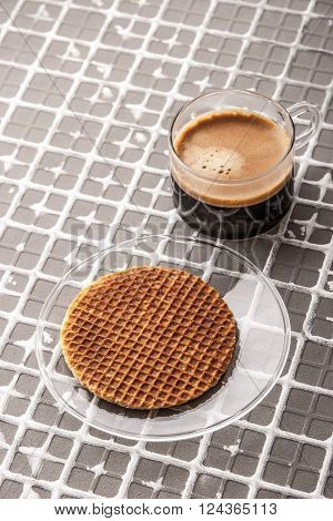 Cup of coffee with wafer on the relief background vertical