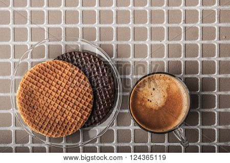 Wafers with cup of coffee on the relief background top view