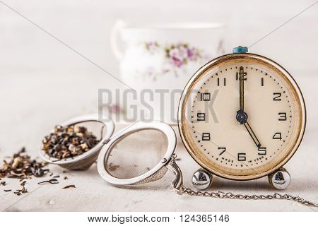 Vintage alarm clock with tea strainer on the white table