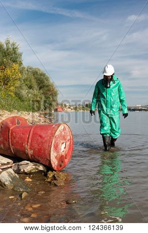 Pollution control official approaching barrel with hazardous waste