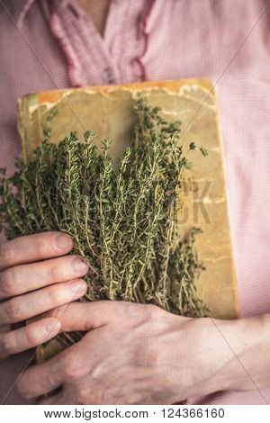 Woman holding old recipe book and herbs