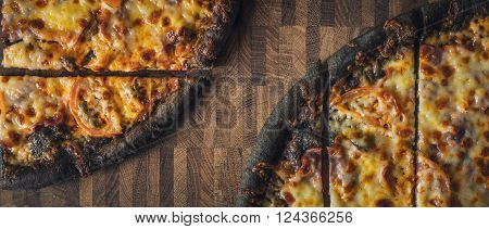 Sliced dough black pizza on the wooden table wide screen