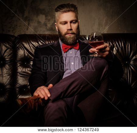 Old-fashioned bearded man sitting in comfortable leather sofa with glass of brandy isolated on gray.