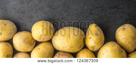 Raw potatoes on the dark stone table wide screen