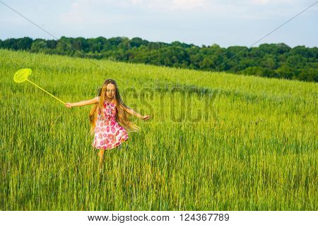 Girl with a butterfly net runs on a glade. Little girl playing in the grass.