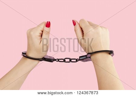 Female hands with re nails in black handcuffs isolated on pink background. Submission trust and passion concept.