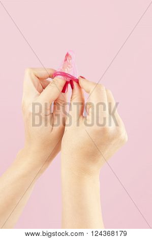 Female hands with red nails holding a pink condom isolated on pink background. Safe sex and birth control concept.