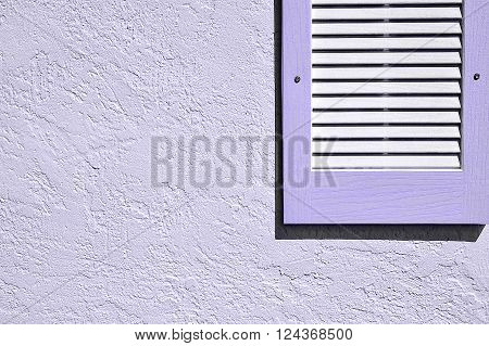 Clean and simple shot of a purple shutter on exterior stucco wall with uncluttered background