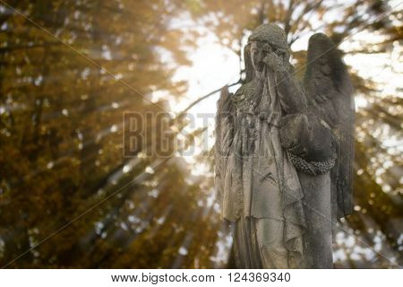 Crying angel statue at old cemetery in autumn. Double exposure.