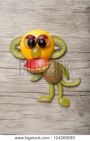 Funny ape made of apple and kiwi on wooden background