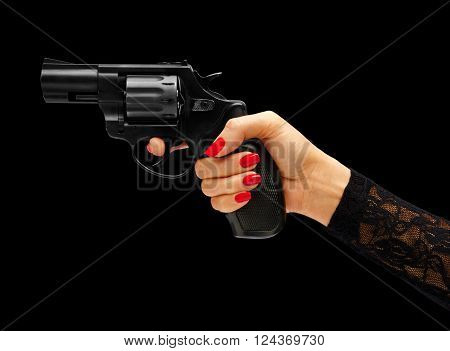 Womens hand aiming revolver gun isolated on black background. Business concept