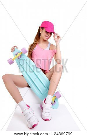 Living a colorful life. Attractive young woman in funky clothes carrying colorful skateboard