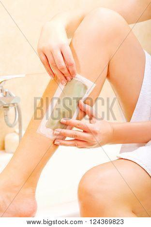 Woman shaving her leg wax
