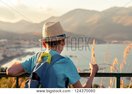 Portrait of pensive serious boy with hat on background of mountains Italy