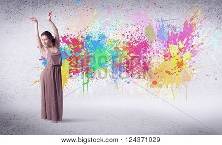 Modern street dancer jumping with colorful paint splashes on back wall concept