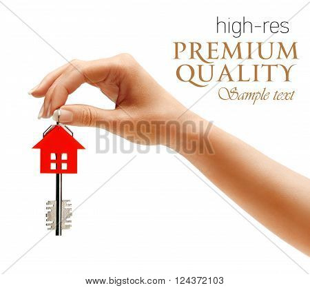 Woman's hand holding house key with keychain in the form of home isolated on white background