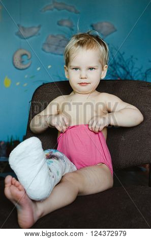 Little child with broken leg. Lifestyle portrait at the home.