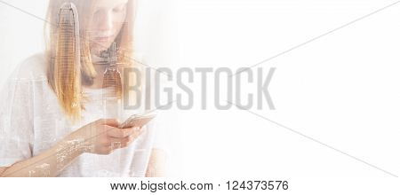 Closeup photo of stylish teenager girl wearing blank t-shirt and looking cell phone. Double exposure, panoramic view contemporary megalopolis background. Space for your business message.