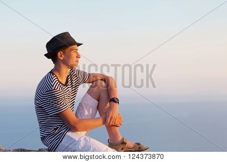 Portrait of serious and pensive young man on sunset sky background outdoor Italy.