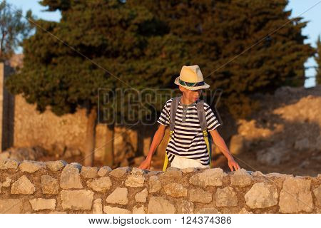 Portrait of pensive serious boy with hat ruins of Temple of Jupiter Italy