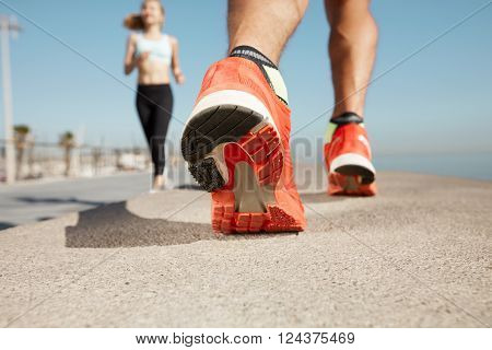 Athlete runner feet running on road closeup on shoe. Man fitness jog workout wellness concept. Man runner legs and shoes in action on road outdoors at road near sea.