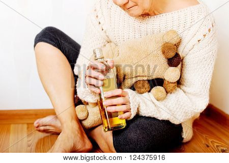 Elderly sad woman sitting in the corner and drinking whiskey