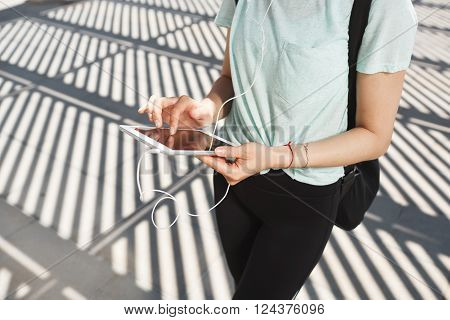 Young asian woman wearing sports wear looking at mobile phone. Female athlete listening music with cell phone. Girl runner enjoying the sun and listen music in earphones from smartphone.