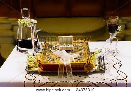ATHENS GREECE - OCTOBER 25 2015: Wedding rings Bible marital Crowns and chalice with wine on a table in preparation for a wedding at church Agia Fotini Ilissos church
