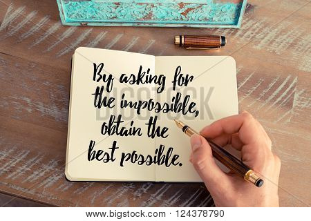 Retro effect and toned image of a woman hand writing on a notebook. Handwritten quote By asking for the impossible, obtain the best possible as inspirational concept image