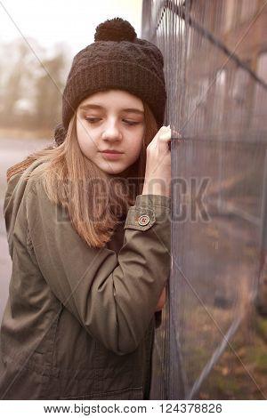 Pretty teenage girl wearing a pom pom hat in an urban setting